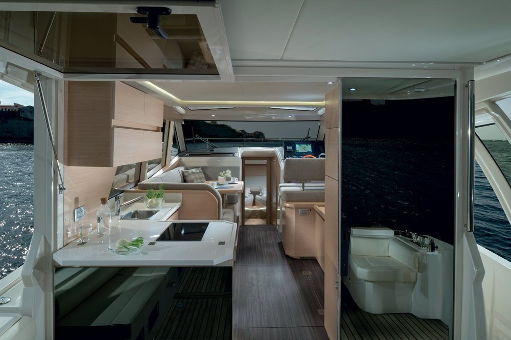 Greenline Yacht Interior Design. A picture shows the very elegant Interior in the salon of the boat, which offers you extreme comfort. You see all: The kitchenarea, the salon and in the back you have a glimpse to the cabin. All is flooded by natural light and offers a 360° panoramic view. All in one level!